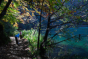 Two children walking on path beside lake, with autumn leaves. Plitvice National Park, Croatia