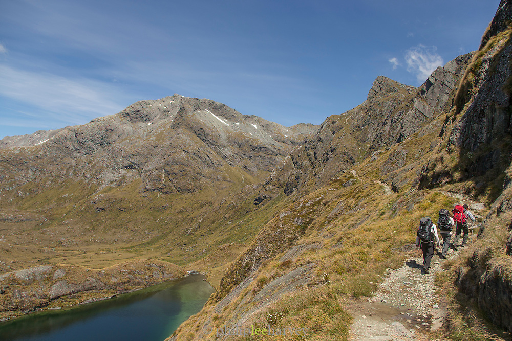 Landscape with view of backpackers hiking near Lake Harris and mountains, Routeburn Track, South Island, New Zealand