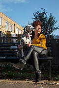 Sally White with her Dalmation, 'Bluebell', pose for their portrait on a memorial bench dedicated to Sally's parents, Cheltenham, England. From project To Those We Love, 2020. Credit: Emily Hutchinson/UoG/PathosImages