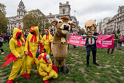 © Licensed to London News Pictures. 24/10/2020. LONDON, UK.  Characters dressed as Donald Trump, President of the United States, a pantomime cow and chlorinated chickens join people in Parliament Square protesting against a post-Brexit trade deal with the USA claiming that, amongst other reasons, the NHS and food standards would be negatively affected.  Photo credit: Stephen Chung/LNP