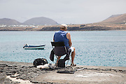 Man sitting fishing from harbour wall Arrecife, Lanzarote, Canary Islands, Spain