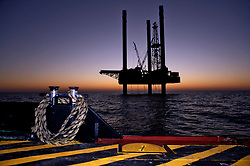 Offshore oil and gas jackup drilling rig at sunset in the Gulf of Mexico viewed from workboat.