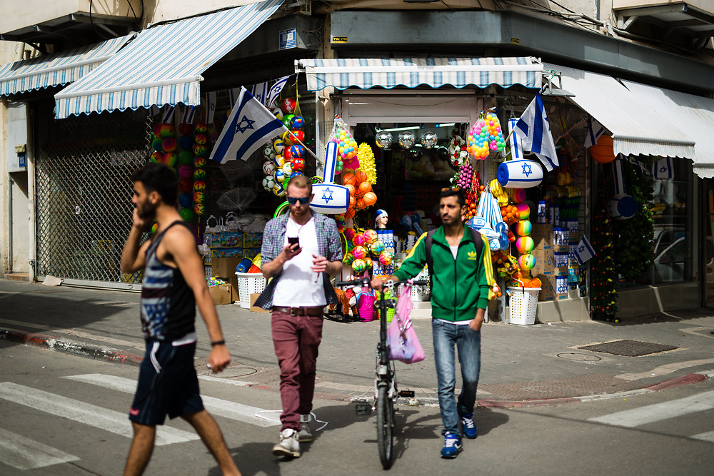 Israelis are seen as they walk past a shop selling Israeli flags and other merchandise ahead of Israel's Independence Day which will be celebrated next week, around the Levinsky Market area in southern Tel Aviv, Israel, on April 16, 2015. The majority of the Levinsky Market vendors are traditional Iranian Jews, many of whom fled the Islamic Republic after Ayatollah Khomeini rose to power in 1979.