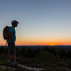 A hiker enjoying the sunset from the summit of Mount Agamenticus in York, Maine.