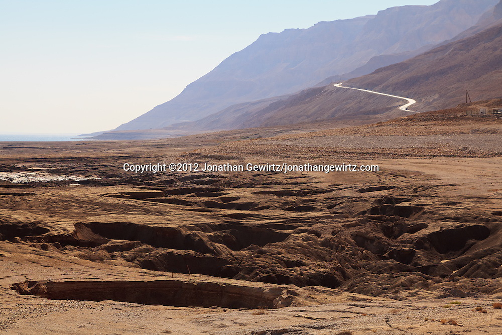 Sinkholes,formed as the Dead Sea's water level has declined, cover an Israeli Dead Sea beach. Highway 90 is visible in the background. WATERMARKS WILL NOT APPEAR ON PRINTS OR LICENSED IMAGES.