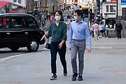 Even though most restrictions have come to an end, and central London is busier than much of the last 18 months as people return to work, for shopping or sightseeing, many people are still wearing face masks especially in busy areas on 11th August 2021 in London, United Kingdom. Many people are wearing face masks in crowded places like this but they are no longer mandatory, while government advice suggests that it is advised to wear a face covering in busy public places inside and on transport, many people are still wearing them outside.