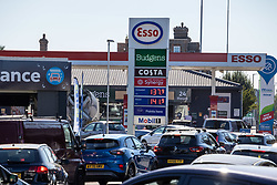Licensed to London News Pictures. 24/09/2021. London, UK. Large queues at an Esso petrol station near the A3 in New Malden this afternoon as oil giants struggle to maintain deliveries due to the lack of HGV drivers continues. Photo credit: Alex Lentati/LNP