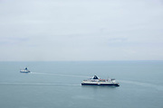 Cross channel ferries P&O and DFDS seaways pass each other outside the port of Dover, United Kingdom.  They cross the 34 kilometres 21 miles  distance of the English Channel, one of the busiest shipping lanes in the world as they transport vehicles and cargo between the ports of Dover, England and Calais, France.