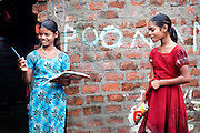 Poonam, 11, (left) is discussing her homework with Jyoti, 12, (right) while standing in the front yard of their family's newly built home in Oriya Basti, one of the water-affected colonies in Bhopal, Madhya Pradesh, India, near the abandoned Union Carbide (now DOW Chemical) industrial complex.