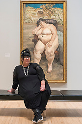 """© Licensed to London News Pictures. 26/02/2018. LONDON, UK. Sue Tilley sits with a painting of herself by Lucian Freud """"Sleeping by the Lion Carpet"""", 1996. """"Preview of """"All Too Human"""", an exhibition at Tate Britain which explores how artists in Britain have stretched the possibilities of paint in order to capture life around them.  The exhibition runs 28 February to 27 August 2018 and includes rarely seen works by Lucian Freud and Francis Bacon.  Photo credit: Stephen Chung/LNP"""