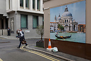 A vaping man strides past a wall picture showing a gondolier and the church of Santa Maria della Salute church in Venice, on 16th March 2017, on the corner of Duke of York Street, in St james's, London, England.