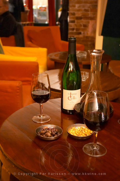 Bottle on a table with wine glasses and decanter in the wine bar Le Cafe du Passage in Paris. Domaine La Jasse Castel. Montpeyroux. Languedoc. France. Europe.