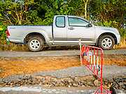 14 JULY 2015 - THAILAND:  A pickup truck drives along a collapsed road in Pathum Thani province. The drought that has crippled agriculture in central Thailand is now impacting residential areas near Bangkok. The Thai government is reporting that more than 250,000 homes in the provinces surrounding Bangkok have had their domestic water cut because the canals that supply water to local treatment plants were too low to feed the plants. Local government agencies and the Thai army are trucking water to impacted communities and homes. Roads in the area have started collapsing because of subsidence caused by the retreating waters. Central Thailand is contending with drought. By one estimate, about 80 percent of Thailand's agricultural land is in drought like conditions and farmers have been told to stop planting new acreage of rice, the area's principal cash crop.      PHOTO BY JACK KURTZ
