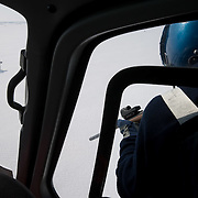 Dr. Steve Amstrup, leaning from a moving helicopter, takes careful aim with his dart gun used to inject immobilizing drug in to a polar bear. Beaufort Sea ice pack. Kaktovik, Alaska.