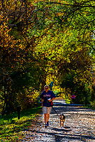 Man running with his dog on the Highline Canal path on an Autumn afternoon, Littleton, Colorado USA.