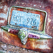 An old license plate has almost completely faded out on the trunk of a car in the Old Car City junkyard in Georgia.