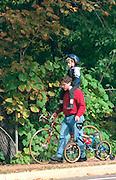 Father and son age 30 and 6 walking at Catholic School Bike A Thon.  St Paul  Minnesota USA