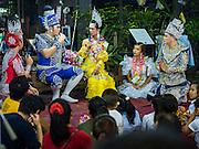 25 SEPTEMBER 2016 - BANGKOK, THAILAND: Residents of the Pom Mahakan community watch Likay performers on stage during a performance in Pom Mahakan Fort. The performance was to support residents of the old fort, who are fighting eviction orders by the city of Bangkok. City officials have made repeated attempts to evict people since Sept 3, 2016, but about 44 families are still living in the community. Likay is a form of popular folk theatre from Thailand. It uses a combination of extravagant costumes, barely equipped stages and vague storylines. The performances depend mainly on the actors' skills of improvisation and the audiences' imagination. There used to be several Likay troupes based in the old fort, but they left the community more than 50 years ago. The troupe that performed Sunday night was an amateur troupe comprised of college students and office workers.      PHOTO BY JACK KURTZ