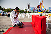 13 APRIL 2013 - BANGKOK, THAILAND: A man prays on the plaza in front of Bangkok's City Hall building on the first day of Songkran. Songkran is the traditional Thai New Year's Festival. It is held April 13-16. Many Thais mark the holiday by going to temples and making merit by giving extra alms to monks or offering extra prayers. They also mark Songkran with joyous water fights. Songkran has been a national holiday since 1940, when Thailand moved the first day of the year to January 1.    PHOTO BY JACK KURTZ