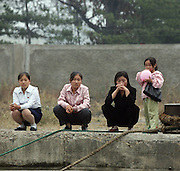 A group of young women sit on a pier in the North Korean border town of Sunuiju, DPRK October 10, 2006. North Korea declared that it has conducted an underground nuclear test ó becoming only the eighth country to do so.  DPRK, north korea, china, dandong, border, liaoning, democratic, people's, rebiblic, of, korea, nuclear, test, rice, japan, arms, race, weapons, stalinist, communist, kin jong il
