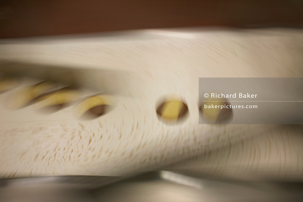 Finished Moments biscuits blur on a conveyor belt at the Delacre production factory in Lambermont, Belgium.