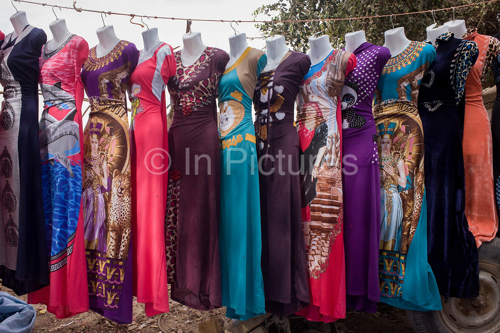 Colourful dress designs hang from a line on a stall at the weekly market at Qurna, a village on the West Bank of Luxor, Nile Valley, Egypt. The latest in patterns for the modern Egyptian woman are being sold in a beautiful line of fashions and styles. Amidst the bustle of this busy regular event, people from many miles around have come to trade and buy their provisions.