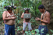 Chief Almir Narayamogo, with his iphone, another with a computer, and another holds a gps reciever, they are mapping in the Surui territory, primary rainforest interior.<br /><br />An Amazonian tribal chief Almir Narayamogo, leader of 1350 Surui Indians in Rondônia, near Cacaol, Brazil, with a $100,000 bounty on his head, is fighting for the survival of his people and their forest, and using the world's modern hi-tech tools; computers, smartphones, Google Earth and digital forestry surveillance. So far their fight has been very effective, leading to a most promising and novel result. In 2013, Almir Narayamogo, led his people to be the first and unique indigenous tribe in the world to manage their own REDD+ carbon project and sell carbon credits to the industrial world. By marketing the CO2 capacity of 250 000 hectares of their virgin forest, the forty year old Surui, has ensured the preservation, as well as a future of his community. <br /><br />In 2009, the four clans and 25 Surui villages voted in favour of a total moratorium on logging and the carbon credits project. <br /><br />They still face deforestation problems, such as illegal logging, and gold mining which causes pollution of their river systems