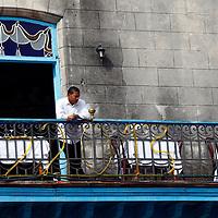 Central America, Cuba, Havana. Waiter watches street from balcony.