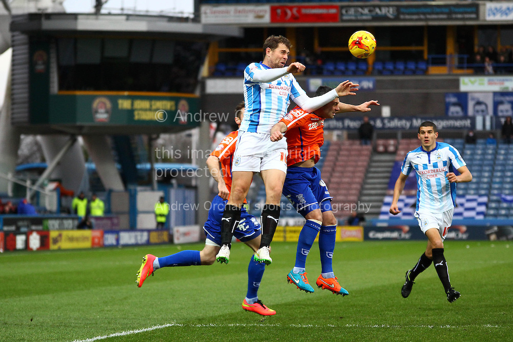 Grant Holt of Huddersfield Town jumps above Mark Hudson of Huddersfield Town but his effort is blocked. Skybet football league championship match, Huddersfield Town v Birmingham city at the John Smith's stadium in Huddersfield, Yorkshire on Saturday 20th December 2014.<br /> pic by Chris Stading, Andrew Orchard sports photography.