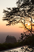 Taung Kalat Buddhist monstery perched atop  a volcanic plug of Mount Popa, an extinct volcano, seen here from a luxury hotel. Near the ancient city of Bagan, Myanmar