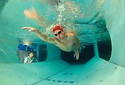 A researcher checks a swimmer for his stroke.