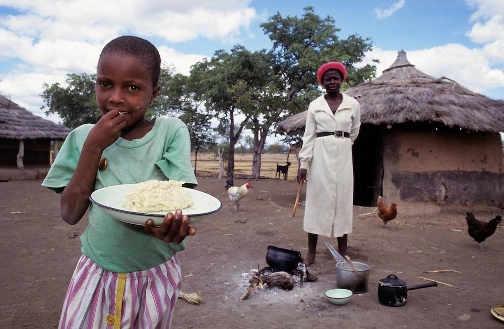 Young girl eating. Rural Zimbabwe, Africa