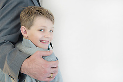 Father holding son, smiling