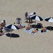 Sunbathers on Ipanema Beach, Rio de Janeiro, looking towards Arpoador point, Rio de Janeiro,  Brazil. 29th July 2010. Photo Tim Clayton.