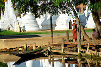 BURMA (MYANMAR) Shan State, Nyaungshwe, Inle Lake. 2006. A young Buddhist monk watches river boats ply by his temple, built half over the waters of Inle Lake.