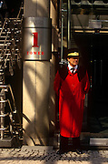 """A doorman in traditional long red overcoat stands outside the Lloyds of London address in the City of London, the capital's heart of the financial district. The post-modern architecture of the insurance underwriters Lloyd's building, home of the insurance institution Lloyd's of London which is located at number 1, Lime Street. Lloyd's is a British insurance market. It serves as a meeting place where multiple financial backers or """"members"""", whether individuals (traditionally known as """"Names"""") or corporations, come together to pool and spread risk. The Lloyds market began in Edward Lloyd's coffeehouse around 1688 and is today the world's leading insurance market providing specialist insurance services to businesses in over 200 countries and territories."""