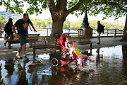 Man pushes a pram through a deep puddle under trees after heavy rain on the riverside walkway. The South Bank is a significant arts and entertainment district, and home to an endless list of activities for Londoners, visitors and tourists alike.