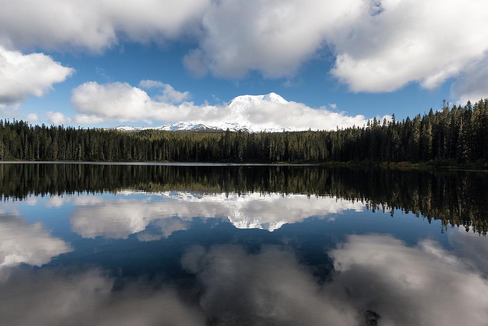 Mt Adams and clouds reflect on the surface of Takhlakh Lake, Washington