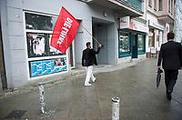 DEU, Deutschland, Germany, Berlin, 19.08.2013:<br />Ein junger Mann läuft mit einer Fahne der Linkspartei durch Schöneberg. Rechts am Bildrand ein Personenschützer des Fraktionsvorsitzenden der Linkspartei. Politiker der Partei DIE LINKE besuchten heute im Rahmen eines Kiez-Spaziergangs verschiedene Einrichtungen in Schöneberg.