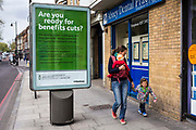 "A young Caucasian woman walks past an information poster from Hackney Council asking: ""Are you ready for benefits cuts?"" on a busy road in Stoke Newington, Hackney, London, UK."