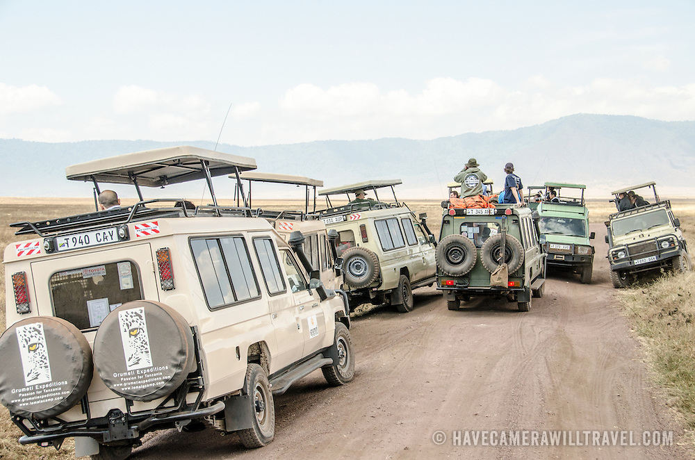 Tourist-laden safari vehicles block at the road while looking at wildlife at Ngorongoro Crater in the Ngorongoro Conservation Area, part of Tanzania's northern circuit of national parks and nature preserves.