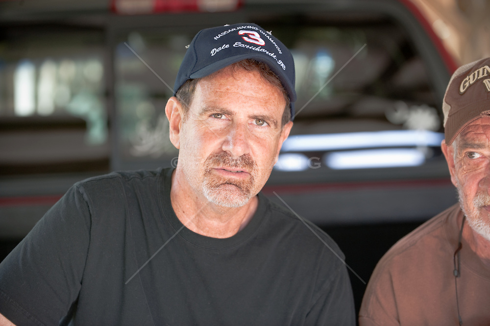Man on back of a truck and another man's partial face