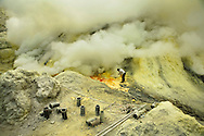 Ijen crater or Kawah Ijen, as it is known locally is Indonesia's famous sulfur belching volcano. It is here that hundreds of men carry out one of the most gruelling and dangerous jobs in the world. The work at Kawah Ijen begins with a 5km climb up to the crater rim and down to the vent, where the sulfur forms. The sulfur is broken into manageable pieces with nothing more than metal rods. The miners have little to none safety equipment and have to battle the toxic sulfuric fumes which are constantly expelled from the vent. Once the sulfur is broken up, it is loaded into bamboo baskets. The weight of the loads starts at 50kg and sometimes exceed 100 kg. The men carry the sulfur up a winding path of crumbling rocks and sand, a step in the wrong direction can mean death. The reward awaits at Ijen sulfur collection base, where the miners can expect an amount of money considerably larger than anything they'd make from most other jobs in rural Java, Indonesia.