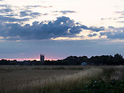 Sunset and clouds over fields and church, Lydd, Kent UK