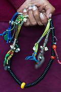 China, Tibet, Lhasa. Detail of hand holding Buddhist prayer beads.