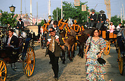 """Each day of the Seville Feria d'Abril, the fiesta begins with the parade of carriages and riders, at midday, carrying Seville's citizens to the bullring, la Real Maestranza...The Feria de abril de Sevilla, """"Seville April Fair"""" dates back to 1847. During the 1920s, the feria reached its peak and became the spectacle that it is today. It is held in the Andalusian capital of Seville in Spain. The fair generally begins two weeks after the Semana Santa, Easter Holy Week. The fair officially begins at midnight on Monday, and runs six days, ending on the following Sunday...For the duration of the fair, the fairgrounds and a vast area on the far bank of the Guadalquivir River are covered in rows of casetas (individual decorated marquee tents which are temporarily built on the fairground). Some of these casetas belong to the prominent families of Seville, some to groups of friends, clubs, trade associations or political parties. From around nine at night until six or seven the following morning, at first in the streets and later only within each caseta, crowds of people party and dance Sevillanas, traditional Flamenco dances, Sevillan style drinking Jerez sherry, or Manzanilla wine, and eating tapas. Men and women dress up in their finery, the traditional """"traje corto"""" (short jacket, tight trousers and boots) for men and the """"faralaes"""" or """"trajes de flamenca"""" (flamenco style dress) for women. The men traditionally wear hats called """"cordobés""""."""
