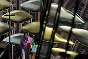 Middle-aged man of south-Asian descent on walkway with the new Olympic kinetic artwork called the Shoal at Stratford. 'The Shoal' at the Stratford Centre, east London, is made up of around 100 titanium clad 'leaves' mounted between 15 and 19 metres high on metal posts. Worth £13.5m, the Shoal is part of The Stratford Town Centre Public Realm Project, designed and manufacturered using 3D technology.