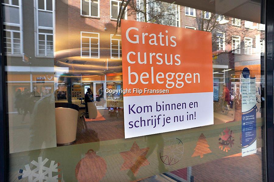 Nederland, Nijmegen, 1-2-2013Tegen het raam van een filiaal, vestiging, kantoor van de SNS bank hangt een reclameposter om gratis een cusus beleggen te volgen.Foto: Flip Franssen/Hollandse Hoogte