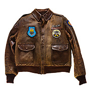 """This type A-2 flight jacket belonged to Henry J. Gerards, a pilot attached to the 570th squadron of the 390th Bomb Group. On the front left of the jacket is the 570th squadron insignia patch, a joker with 4 aces behind it. Above the patch is the name plate which reads """"H.J. Gerards"""", Gerards' silver Army Air Corp wings are attached to the jacket above the name plate. The 390th Bombardment Group's insignia patch is attached to the front right of the jacket. The 8th Air Force insignia patch is attached to the left sleeve of the jacket. There is no artwork on the back of the jacket. Gerards flew 23 missions over Europe as a member of the 570th squadron. On his 23rd mission, a raid over Magdeberg on May 28, 1944, Gerards aircraft was shot down. Gerards was then taken prisoner by the Germans and was held at Stalag Luft 3, a Luftwaffe prisoner of war camp. He was a prisoner of war for a year and was released at the conclusion of WWII."""