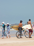 Surfers walk along the beach in the new town at Essaouira, Morocco